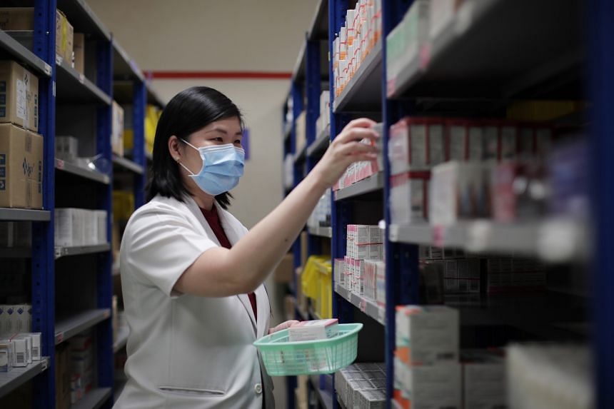 Principal pharmacist Chong Yi San, 41, getting the medications for outpatients at TTSH's pharmacy.