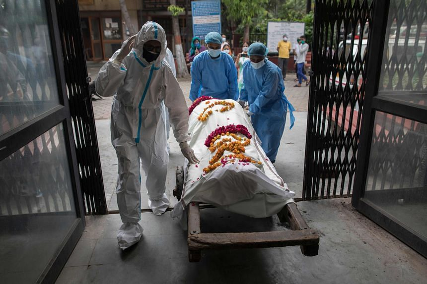 Healthcare workers (in blue) taking the body of a Covid-19 victim, accompanied by a relative, to the Nigambodh Ghat cremation ground in New Delhi on Saturday. As of yesterday morning, India's official death toll stood at 56,706.