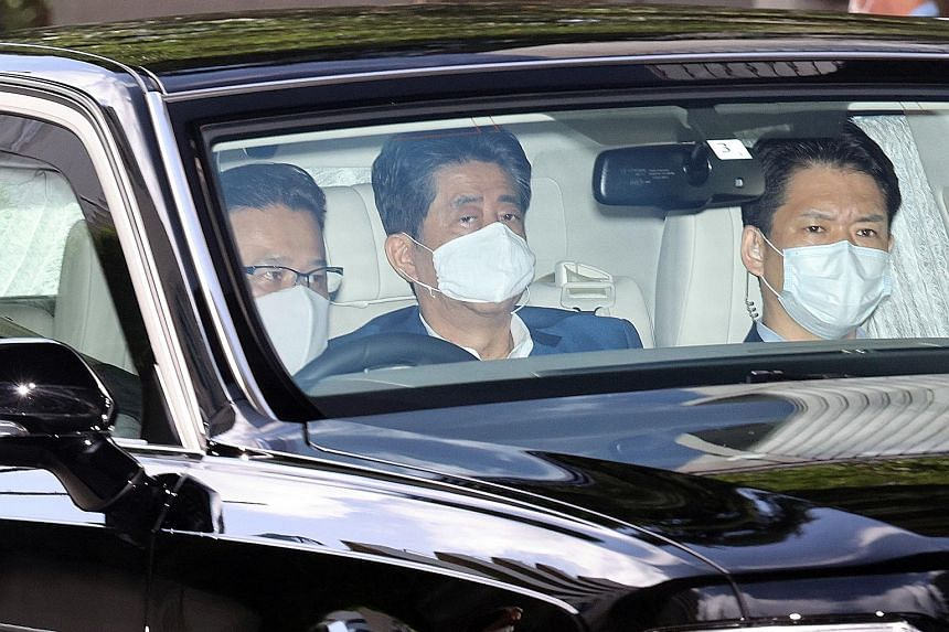 Japanese Prime Minister Shinzo Abe (centre) arriving at Keio University Hospital in Tokyo yesterday. PHOTO: EPA-EFE