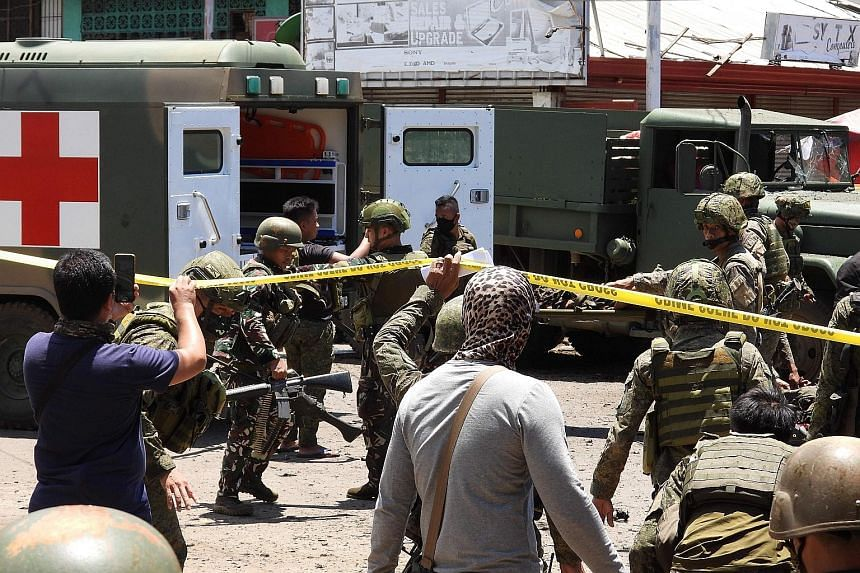 Soldiers carrying away some of the victims after a bomb explosion next to a military truck in the town of Jolo in the Philippines' Sulu province yesterday. At least six soldiers and six civilians were killed in the blast. A second explosion happened