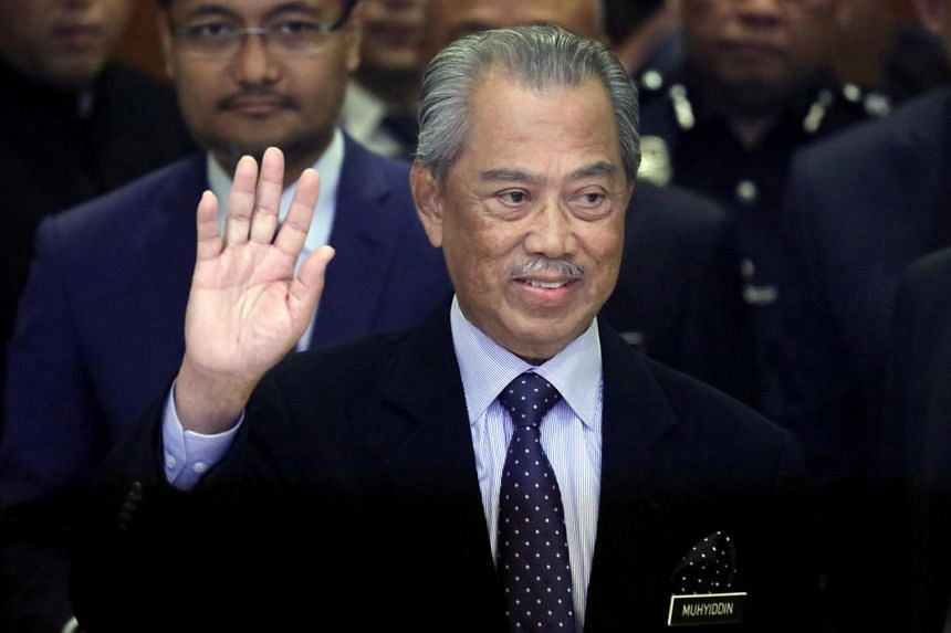 A file photo on March 9, 2020, showing Malaysian Prime Minister Muhyiddin Yassin waving to reporters before his Cabinet announcement in Putrajaya.