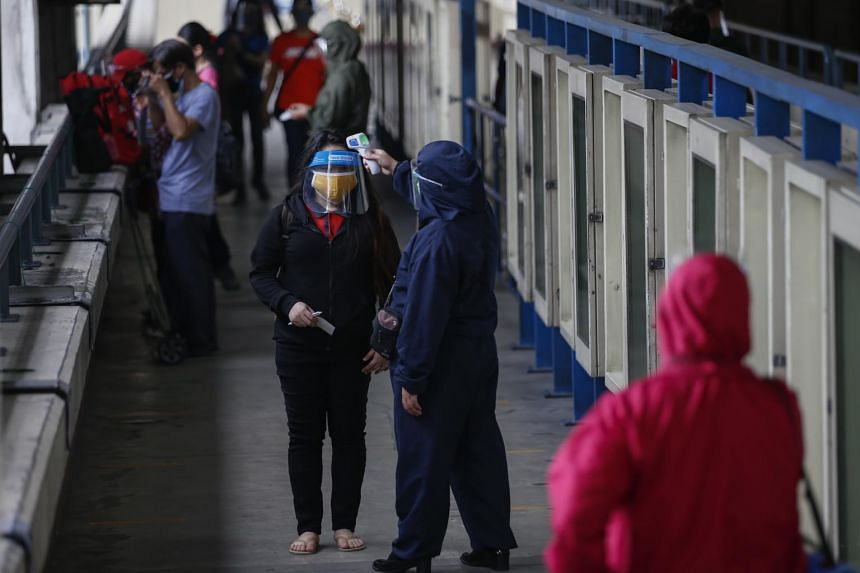 A commuter undergoes a temperature check at the entrance of a Metro Rail Transit station in Quezon, Philippines, on Aug 19, 2020.