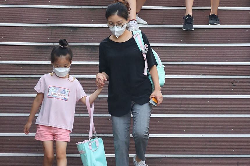 A mother walking her daughter to an elementary school in Seoul yesterday. All students, except for high school seniors, in the cities of Seoul and Incheon and the province of Gyeonggi will take classes online until Sept 11. PHOTOS: AGENCE FRANCE-PRES