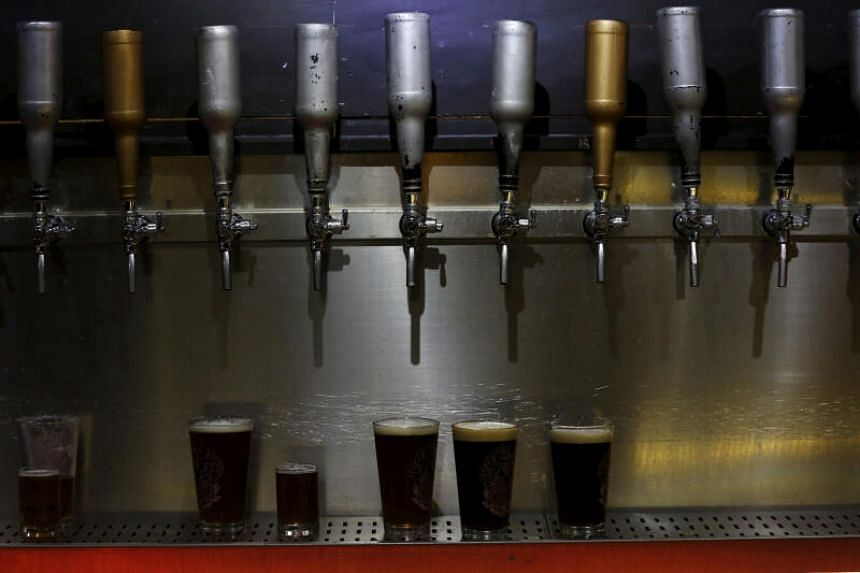 Glasses of craft beer are placed underneath beer taps at a microbrewery in Beijing on March 6, 2016.