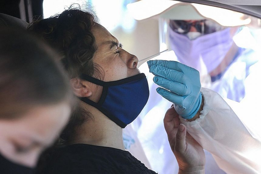 A motorist undergoing a Covid-19 nasal swab test at a drive-in testing centre in Los Angeles earlier this month.