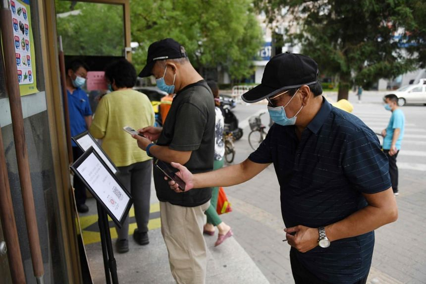 A man scans a QR code to show his health and travel status on a phone app before being allowed to enter a supermarket in Beijing on June 22, 2020.