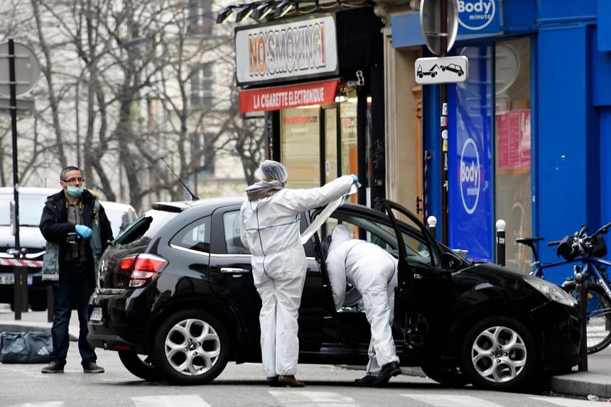 In a photo taken on Jan 7, 2015, French police officers and forensic experts examine the car used by gunmen Cherif Kouachi and his brother Said Kouachi.