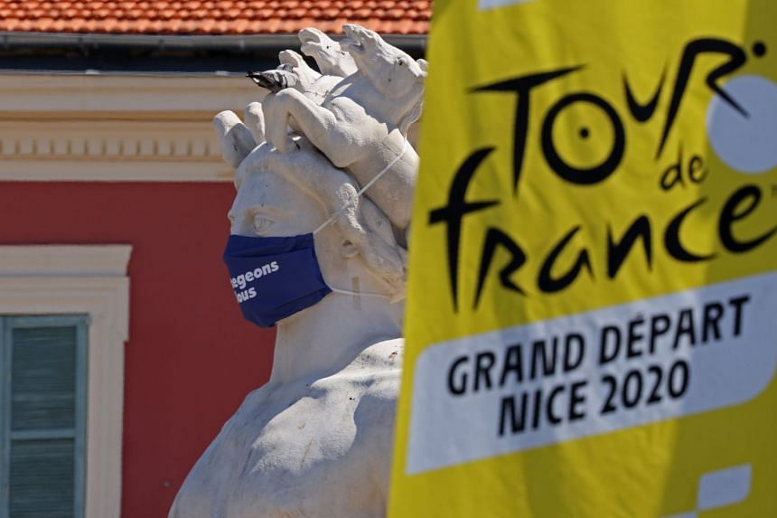 The logo of the 2020 Tour de France is seen next to a masked statue in the French Riviera city of Nice on Aug 26, 2020.
