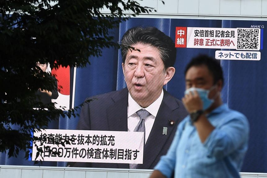 A man walks past a large screen showing Japan PM Shinzo Abe's live press conference in Tokyo on Aug 28, 2020.