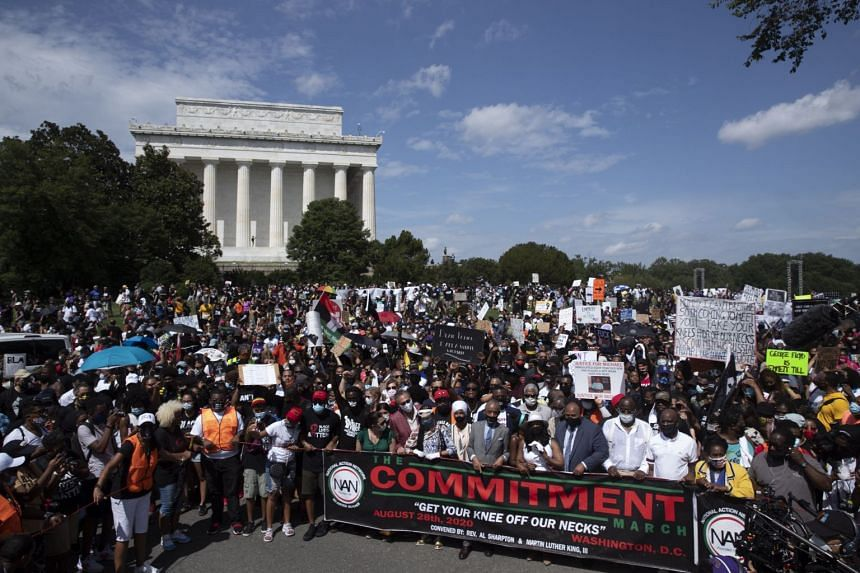 Reverend Al Sharpton (front, centre) particiaptes with crowds marching from the Lincoln Memorial (seen behind) to the Martin Luther King Jr Memorial.