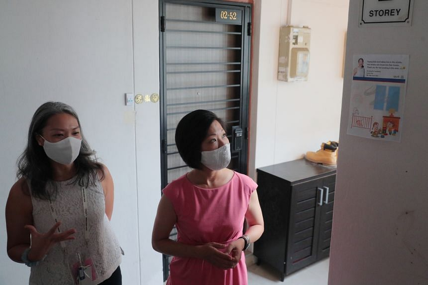 Nee Soon GRC MP Carrie Tan (left) and Senior Minister of State for National Development Sim Ann viewing an advisory on smoking put up at Block 851 Yishun Street 81.