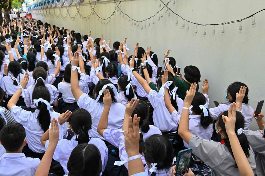 Students salute and wear knotted white ribbons as they take part in a protest in front of Bangkok's Education Ministry on Aug 19, 2020.