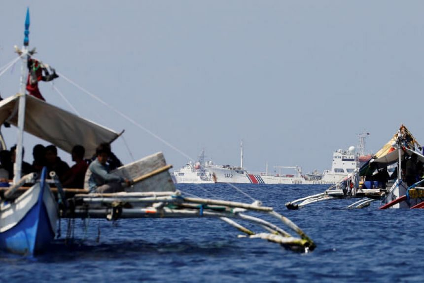 China Coast Guard vessels patrol past Philippine fishing boats at Scarborough Shoal, on April 5, 2017.