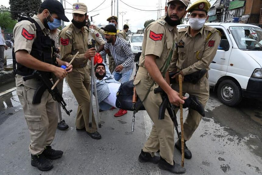 A Kashmiri Shiite Muslim man is detained by Indian police as devotees defy restrictions for a Muharram procession in Srinagar on Aug 28, 2020.