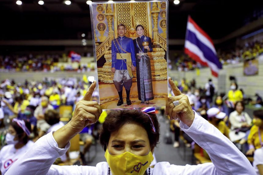 A person holds a picture of Thai King Maha Vajiralongkorn with Queen Suthida during a rally in Bangkok, on Aug 30, 2020.