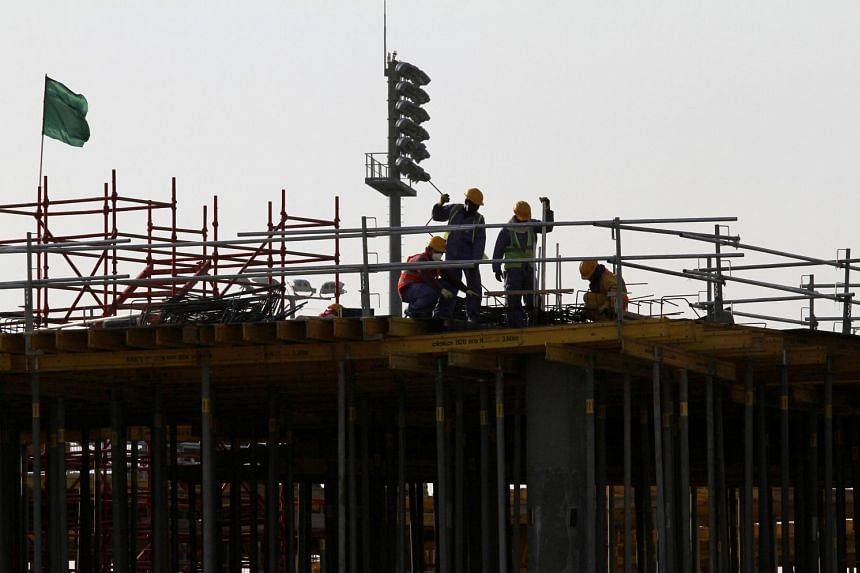 Migrant labourers work at a construction site in Doha.