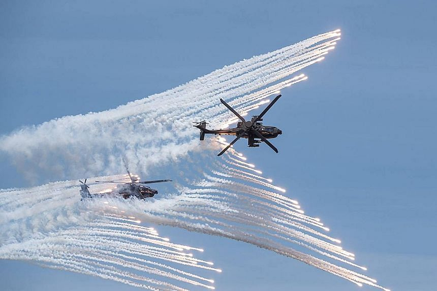 Rockets (above) being launched from a domestically manufactured multiple rocket system and two US-made AH-64E attack helicopters (left) releasing flares during a Taiwanese military drill in Taichung last month. The exercises aimed to demonstrate how