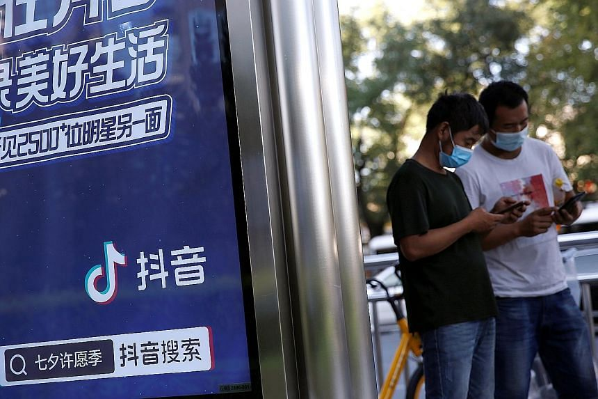 An advertisement for Douyin, as TikTok is known in China, at a bus stop in Beijing. The country's latest export curbs ensnare TikTok and potential US buyers including Microsoft and Oracle. PHOTO: REUTERS