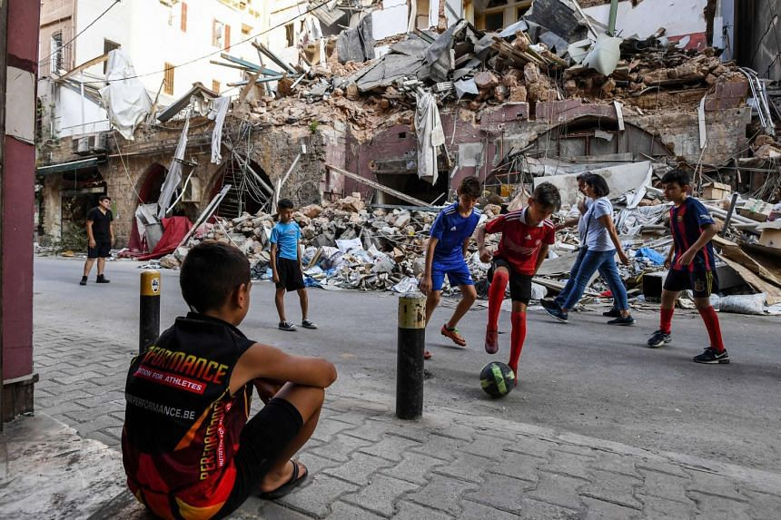 Children play with a football in Beirut, amid buildings destroyed by a massive port blast which devastated the city.