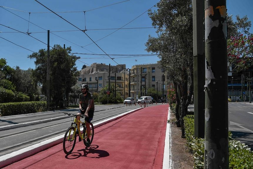 A man rides along a newly created bicycle and pedestrian zone in the center of Athens, on June 11, 2020.