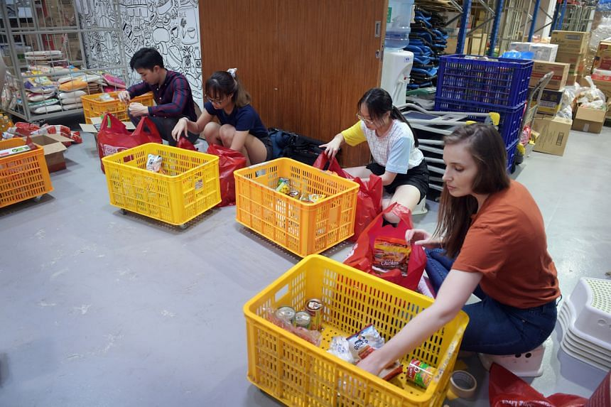 Volunteers and staff pack food for distribution to beneficiaries.