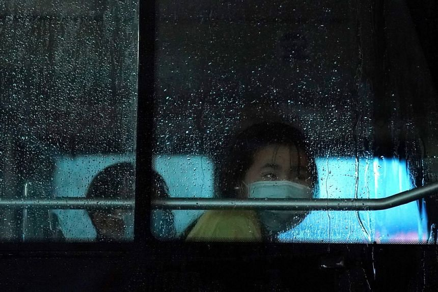 A passenger rides on a bus amid rainfall in Beijing, China.