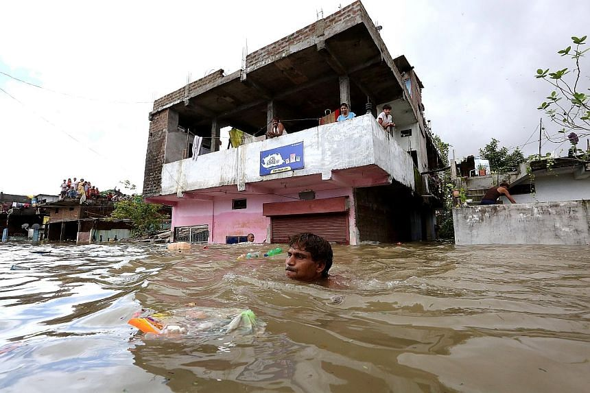 A man trying to save his belongings (top) in the flood-hit area of Hoshangabad (above), 80km from Bhopal, India. Floods around the country were caused by heavy rain during the annual monsoon season, which began around June in South Asia and ends this
