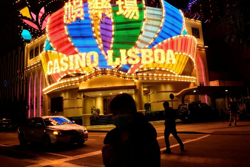 In a photo taken on Feb 4, 2020, people wearing masks walk in front of Casino Lisboa, in Macau, before its temporary closing.