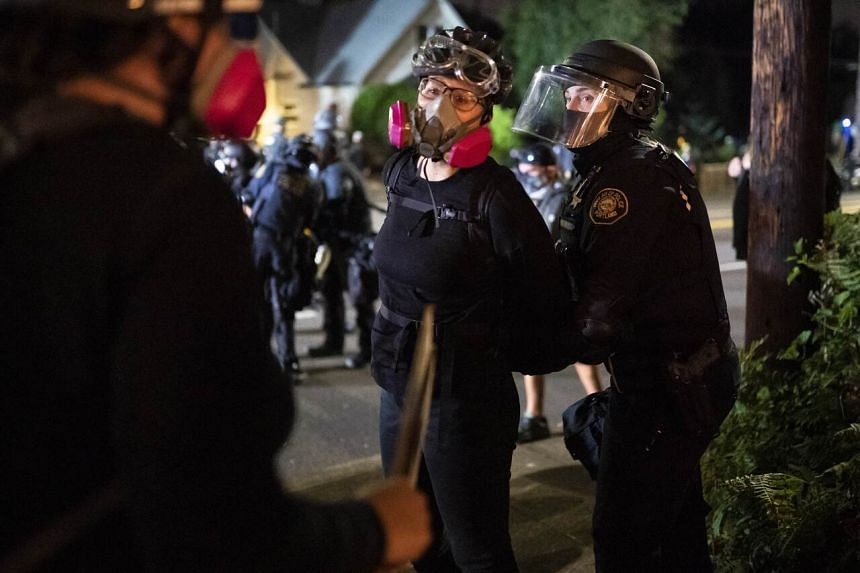 A protester is arrested by a Portland police officer on Aug 30, 2020.