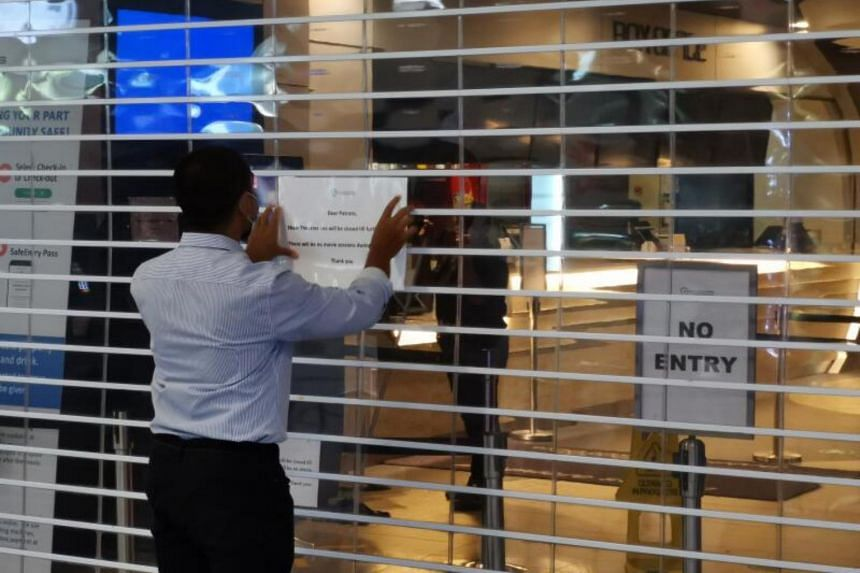 Shaw Theatres staff putting up a closure notice at the Nex outlet on Aug 31, 2020.