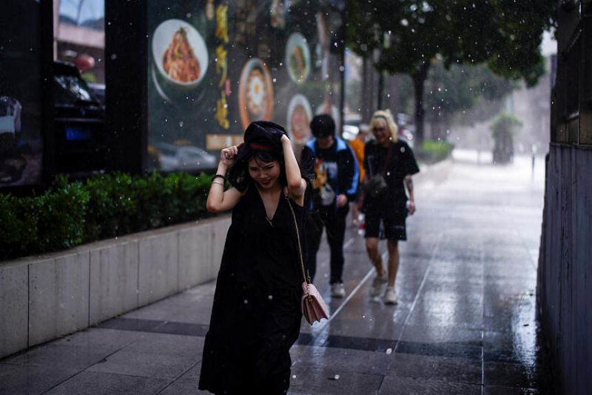 A woman reacts as the rain falls on her in Shanghai on Sept 1, 2020.