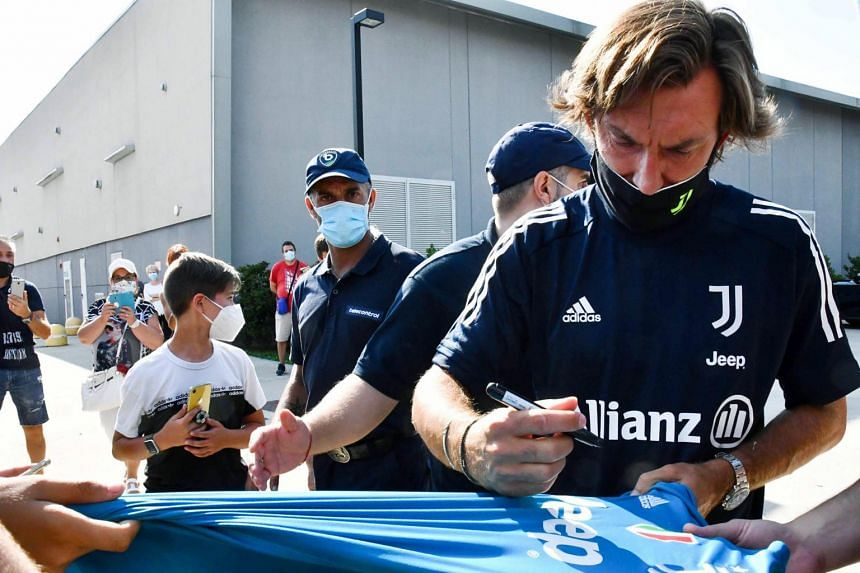 Juventus head coach Andrea Pirlo signing autographs after arriving for his first training session, in Turin, Italy, on Aug 24, 2020.