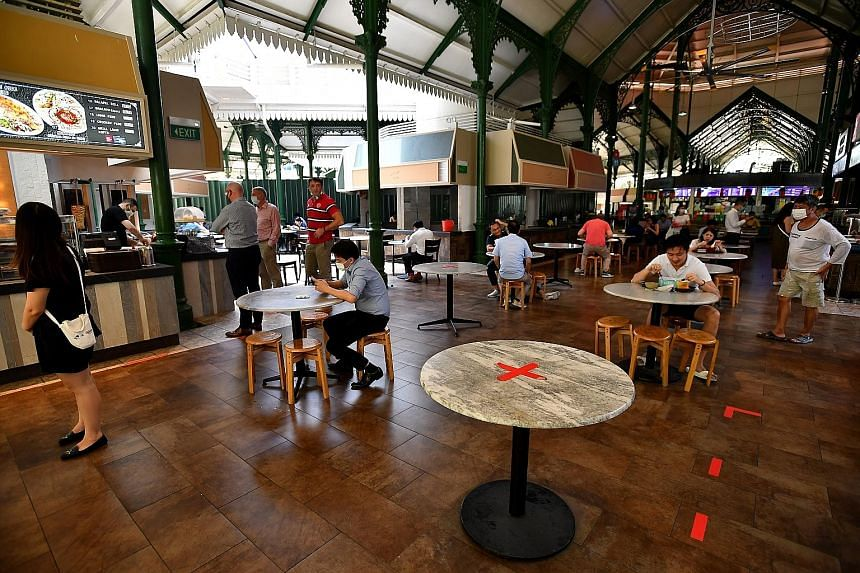 Diners at Lau Pa Sat food centre on Tuesday. Prime Minister Lee Hsien Loong, citing a recent survey by The Straits Times showing almost half of the respondents being tired of pandemic safety measures such as having to wear a mask, warned that the cor