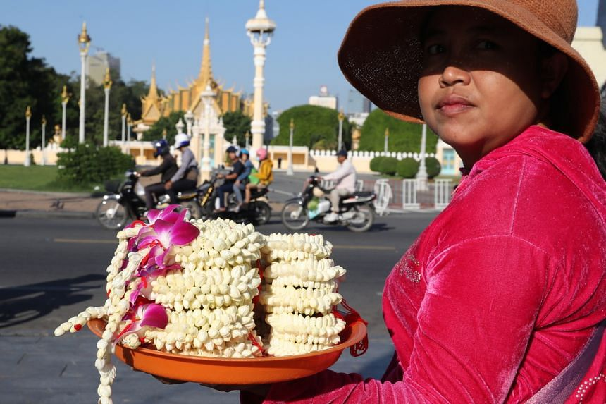 A Cambodian woman selling flowers at a park in front of the Royal Palace in Phnom Penh, Cambodia.