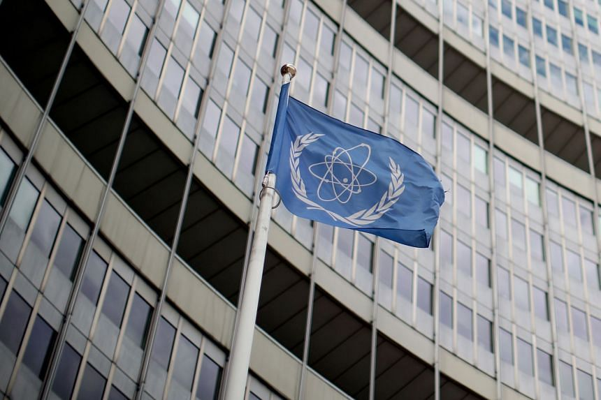 A flag with the logo of the International Atomic Energy Agency flutters in front of its headquarters in Vienna, Austria.