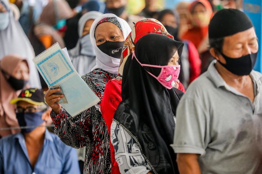 People wearing face masks queue for social assistance packages in Medan.