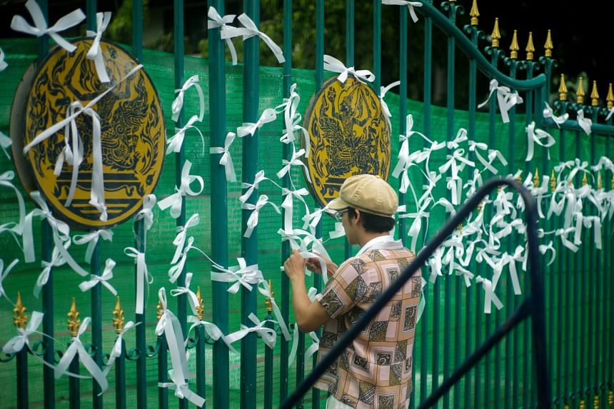 A protester ties white ribbons at the gate of Remand Prison to call for the release of Anon Nampa and Panupong Jadnok, in Bangkok, on Sept 4, 2020.