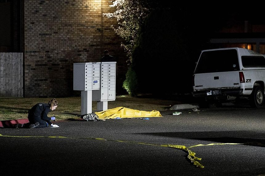 An investigator working near a tarpaulin covering the body of a man, reportedly Michael Forest Reinoehl, after he was shot dead by law enforcement officers on Thursday in Washington.