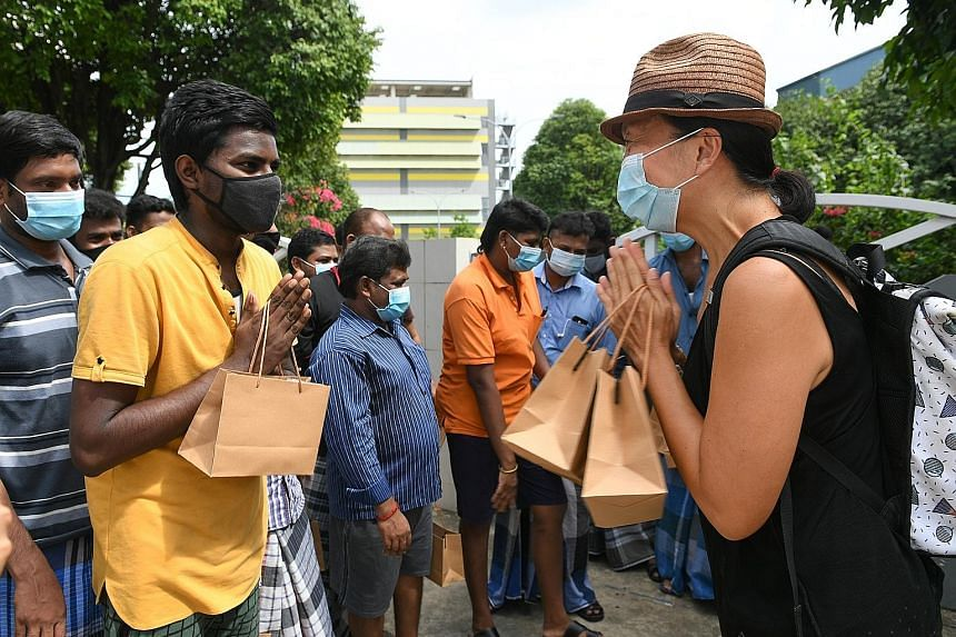 Former Nominated MP Anthea Ong giving self-care kits to migrant workers in July. The pandemic has led Singaporeans to be more appreciative of foreign and front-line workers, says Senior Minister of State Sim Ann. ST PHOTO: SHINTARO TAY