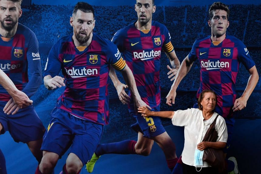 A woman touches Messi's hand on a poster outside Barcelona's Camp Nou stadium on Sept 4, 2020.