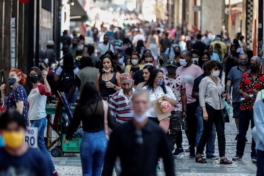 People wearing face masks walk in downtown Sao Paulo on Sept 3, 2020.