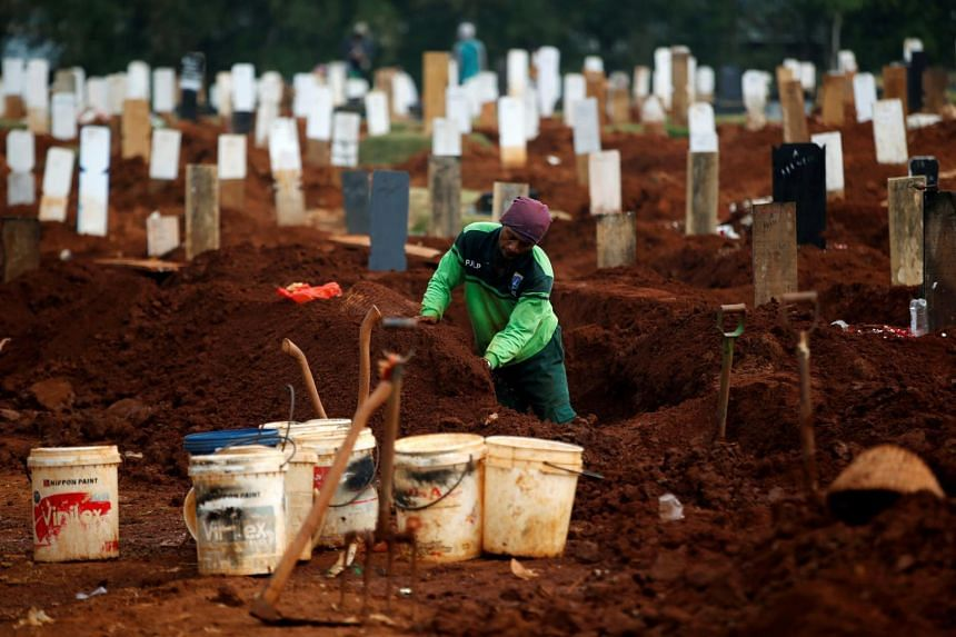 A worker prepares new graves for Covid-19 victims at the Pondok Ranggon cemetery in Jakarta.