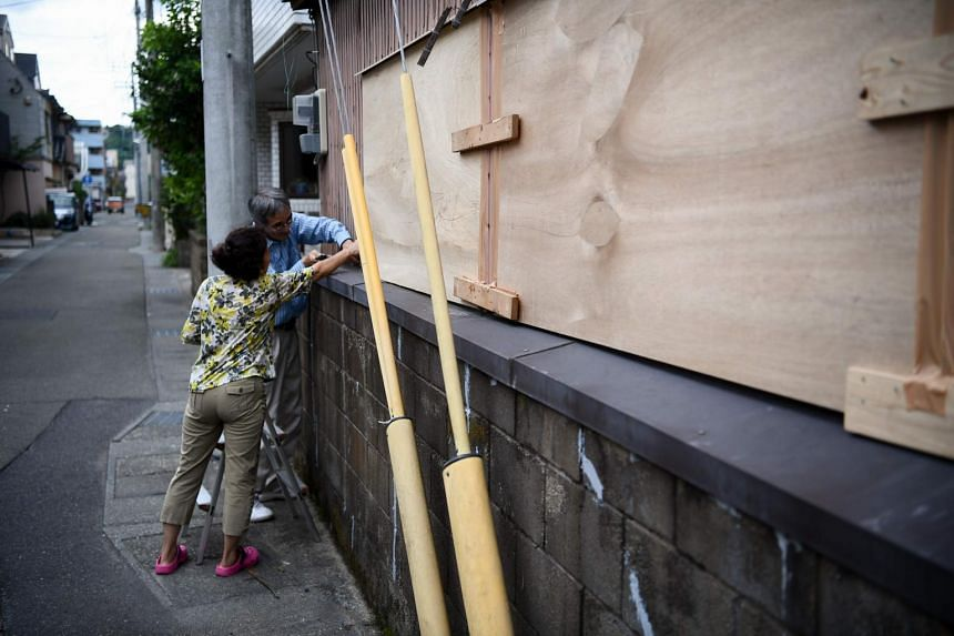 People barricade a house before Typhoon Haishen approaches in Kagoshima, on Sept 5, 2020.