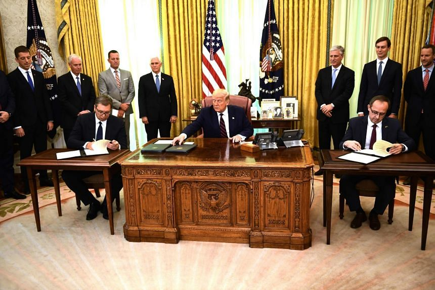 Trump watches as Kosovar Prime Minister Avdullah Hoti (right) and Serbian President Aleksandar Vucic (left) sign an agreement on opening economic relations.