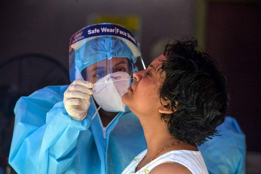 A health official collects nasal swab samples from a woman at a primary health centre in Siliguri on Sept 5, 2020.