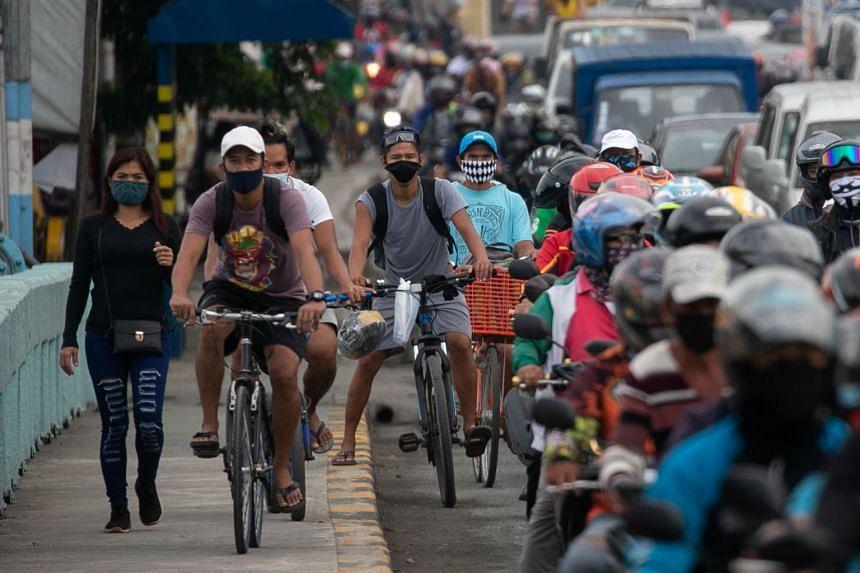 Cyclists bike on a sidewalk in Manila.
