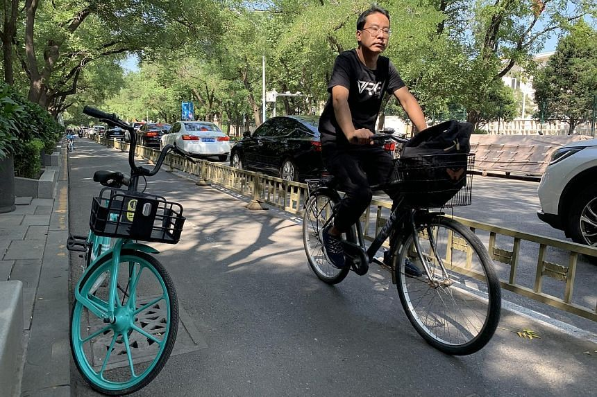 A cyclist in downtown Beijing. Shared bicycle service companies such as Meituan and Hellobike have seen a steady rise in both the frequency and length of trips taken by users.