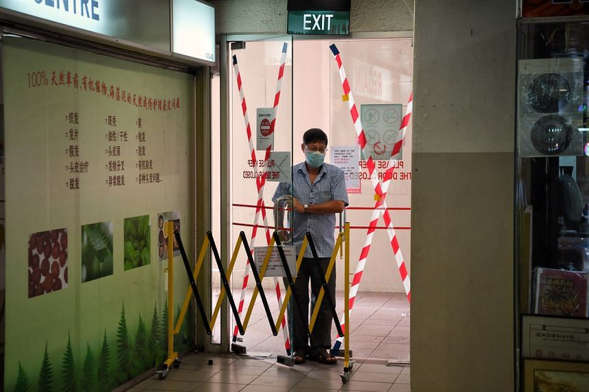 A man enters through a barricaded doorway on the third level of People's Park Centre on Sept 3, 2020.