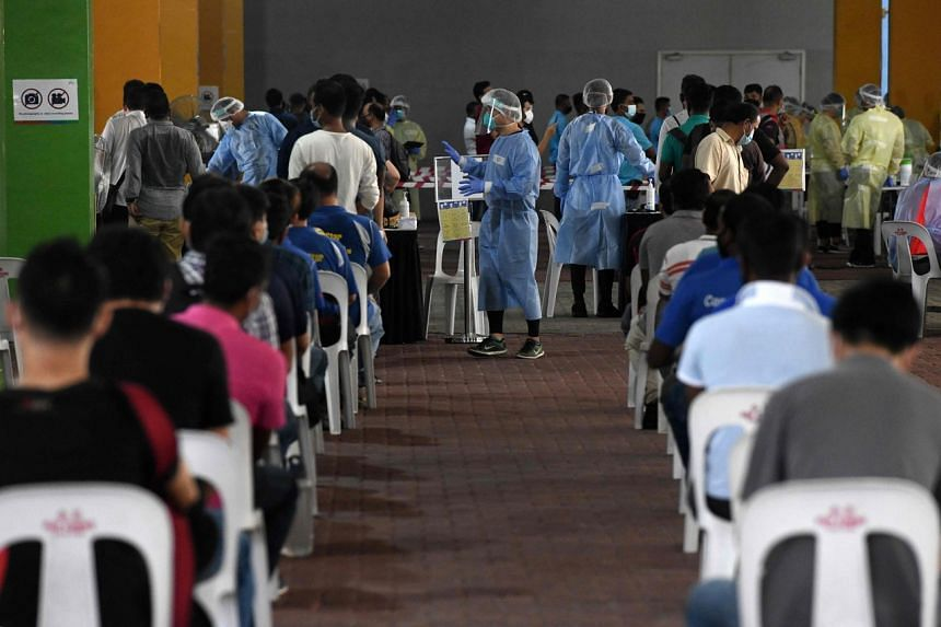 Essential workers waiting to take swab tests for Covid-19 in Singapore on June 10, 2020.