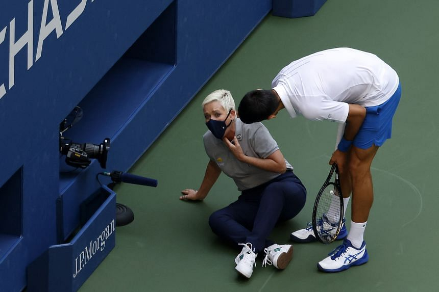 Novak Djokovic (right) tries to help a linesperson after hitting her with a ball in the throat in New York, on Sept 6, 2020.